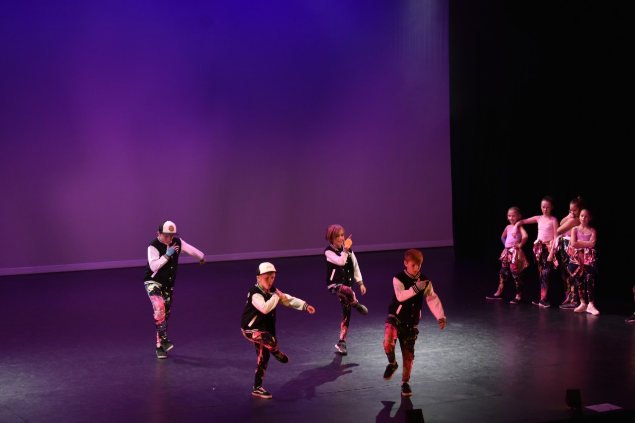 4 boys are dancing centre stage and 4 girl dancers are standing to side stage.