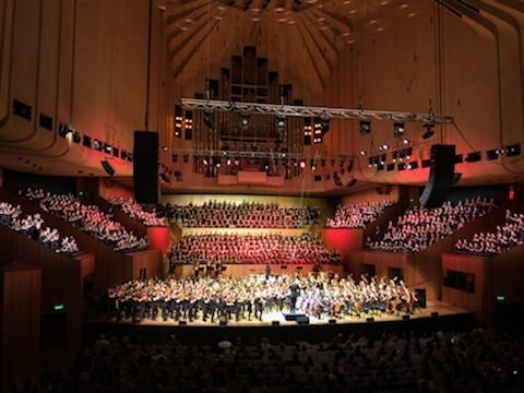 A large group of students are performing in the Opera House.